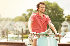 Young man riding vintage scooter in marina Stock Image