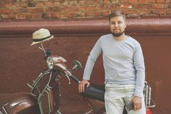 young man riding a vintage scooter in the park royalty free stock photography