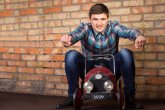 Young Man Riding on Vintage Toy Car. Close up Young Handsome Man in Casual Outfit Riding on Vintage Toy Car on a Brick Wall Background. Emphasizing Racing Stock Photos