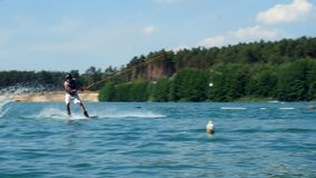 Young man Riding Wakeboard On Lake. Looks at camera training wake boarding stunt. A Man Rides His Wakeboard At A Cable Park, Slow Motion. Sportsman training wake stock footage