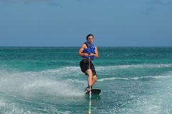 Young Man Riding a Wakeboard off the Coast of Aruba Stock Image