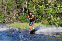 Young man riding wakeboard on summer lake Stock Photo