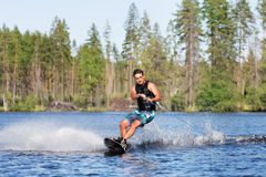Young man riding wakeboard on summer lake Royalty Free Stock Images
