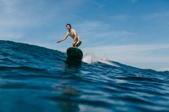 Young man riding waves on surfboard. On sunny day royalty free stock photos