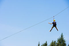 Young Man Riding On Zip Line. Rear view of young man riding on zip line against blue sky royalty free stock image