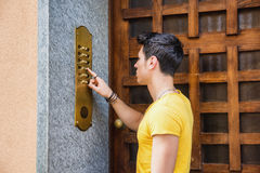 Young man ringing doorbell and talking on speaker Stock Image