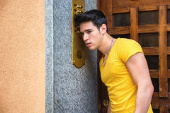 Young man ringing doorbell and talking on speaker Stock Images