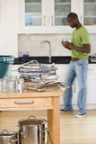 Young man rinsing jars in kitchen by newspapers, empty jars and cans for recycling on side (differential focus) Royalty Free Stock Photos