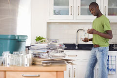 Young man rinsing jars in kitchen, recycling on side, smiling, side view royalty free stock photo