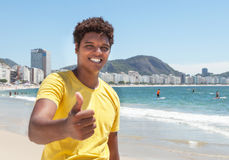 Young man from Rio in a yellow shirt showing thumb at Copacabana Royalty Free Stock Photography