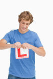 Young man ripping a learner driver sign Royalty Free Stock Image