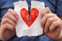 Young man ripping red heart on a piece of paper. Royalty Free Stock Image