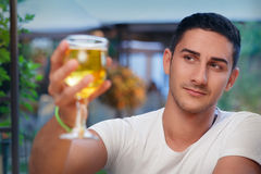 Young Man Rising a Glass in a Bar Stock Photo