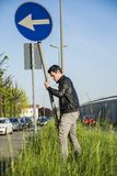Young Man with Road Sign in Long Roadside Grass Stock Image