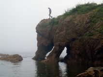 Young man on the rock. Young hiking man on foggy day the elephant rock against sea landscape Stock Photo