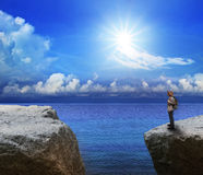 Young man on rock cliff end of way Royalty Free Stock Image