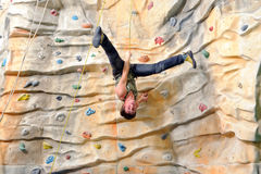 Young man on rock wall Stock Photography