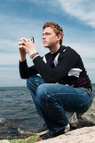 Young man on the rocks on sea background Stock Photos