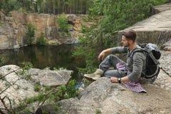 Young man on rocky mountain near lake. Camping season royalty free stock photography