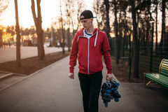 Young man with roller skates in hands. Walking in city park. Male rollerskater leisure Royalty Free Stock Image