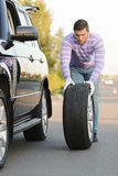 Young man rolling a spare wheel Royalty Free Stock Photo