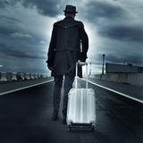 Young man with a rolling suitcase, with a dramatic effect Stock Images