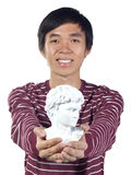 Young man with Roman bust in his hands Royalty Free Stock Photography