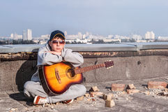 Young man on the roof with a guitar Stock Images
