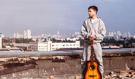 Young man on the roof with a guitar Royalty Free Stock Image