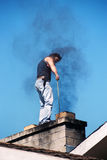 Young man on the roof of the house. Young man standing on the roof of the house,cleaning the chimney Stock Image