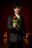 Young  man with rose in black shirt on red Stock Image
