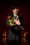 Young  man with rose in black shirt on red Stock Photos