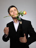 Young man with rose flower and vine bottle Royalty Free Stock Photography