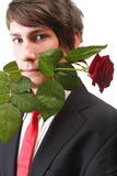Young man with rose in his teeth isolated Stock Photos