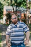 .Young man with round glasses and overweight in the park. Young man with round glasses and overweight in the park stock photo