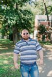 .Young man with round glasses and overweight in the park. Young man with round glasses and overweight in the park royalty free stock photo