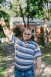 .Young man with round glasses and overweight in the park. Young man with round glasses and overweight in the park stock image