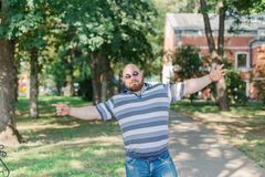 .Young man with round glasses and overweight in the park. Young man with round glasses and overweight in the park stock images