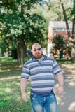 .Young man with round glasses and overweight in the park. Young man with round glasses and overweight in the park royalty free stock image