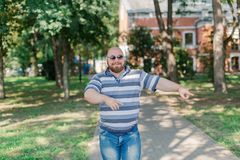 .Young man with round glasses and overweight in the park. Young man with round glasses and overweight in the park royalty free stock photos