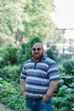 .Young man with round glasses and overweight in the park. Young man with round glasses and overweight in the park royalty free stock photography