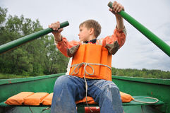Young man rowing a boat. On the river Royalty Free Stock Photo