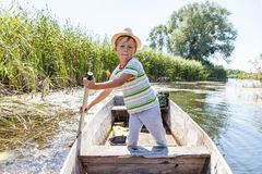 Young man rowing a boat. Young boy rowing oar standing in boat on the river Stock Photo
