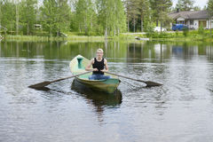 Young man rowing a boat on a lake stock images