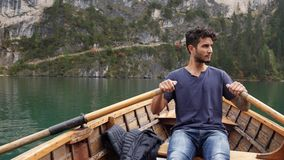 Young man rowing in boat on mountain lake stock footage
