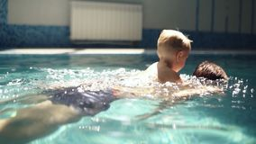 Young man rowing under the water with his blonde son on the back. Little boy is above the water. Indoors swimming pool. Slow motion stock video
