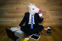 Funny unicorn in a suit and tie smiles and drinks coffee. Young man in rubber mask sits on the floor against a wall and works at home office. Funny unicorn in a Royalty Free Stock Photography