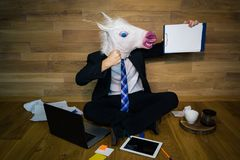 Unicorn in a suit and tie smiles and shows his power. Young man in rubber mask sits on the floor against a wall and works. Unicorn in a suit and tie smiles and Royalty Free Stock Images