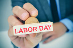 Young man with a rubber stamp with the text labor day Royalty Free Stock Photography
