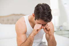Young man rubbing his eyes in bed Stock Images